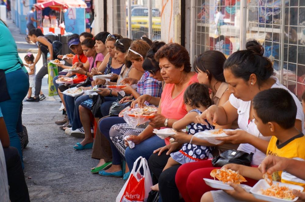 Fila de gente comiendo frente un puesto ambulante de comida, en el centro histórico.