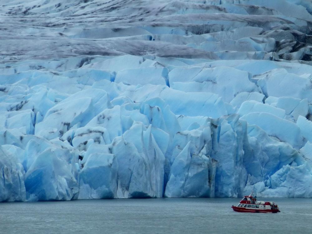 El barco de turistas es diminuto en comparación con el enorme frente del glaciar.